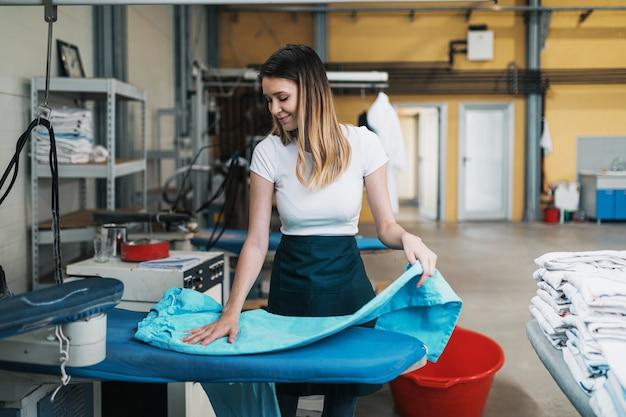 Donna con ferro che lavora al negozio di stiratura. impresa di pulizie.