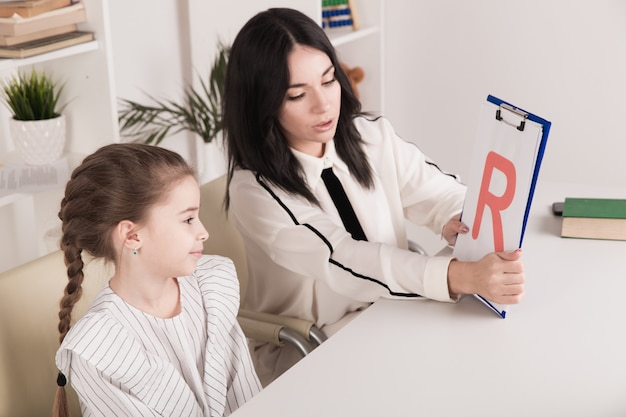 Donna con discorso di formazione ragazza bambino insieme seduto nella stanza bianca.