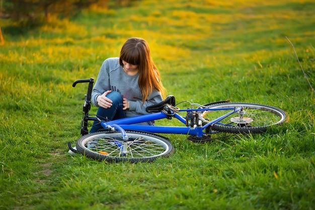 Donna con dolore al ginocchio dopo il ciclismo nel parco al tramonto