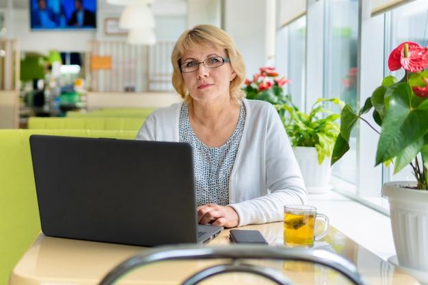 Una donna con un laptop sta lavorando in un ufficio. una donna di mezza età è una donna d'affari in un caffè. fa il lavoro.