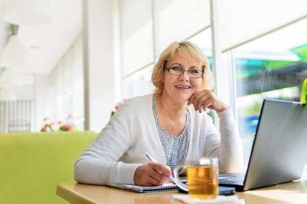 Una donna con un laptop sta lavorando in un ufficio. una donna di mezza età è una donna d'affari in un caffè. sorride e scrive sul suo taccuino.