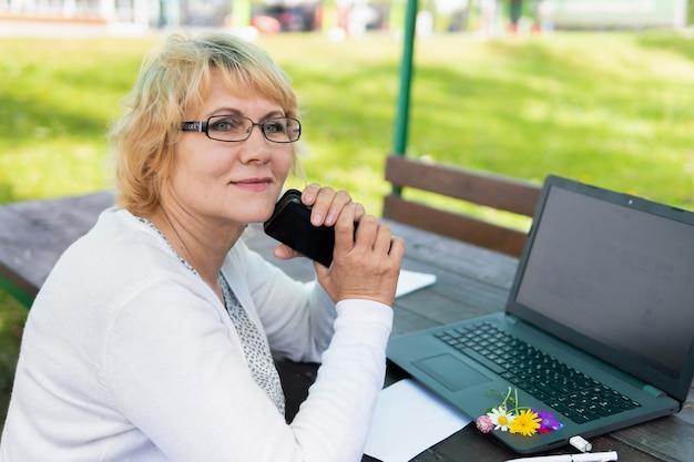 Una donna con un laptop guarda un documento in un bar, in ufficio