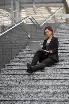 Donna con laptop sulle scale