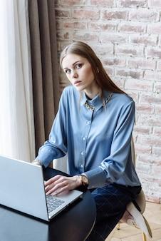 Donna con il computer portatile al tavolo