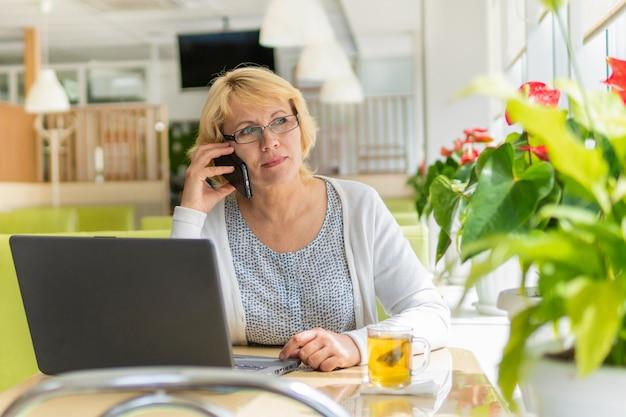 Una donna con un laptop lavora in un bar in ufficio, è una libera professionista e un uomo d'affari