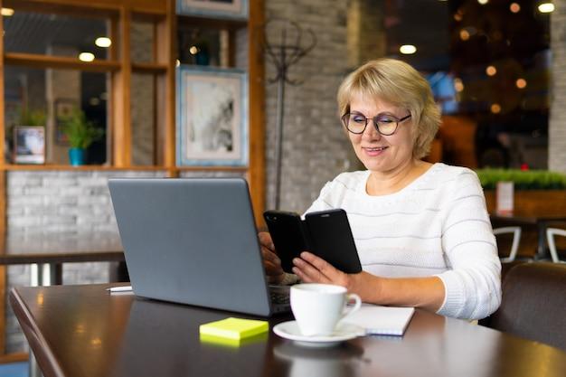 Una donna con un laptop lavora in un bar in ufficio è una libera professionista
