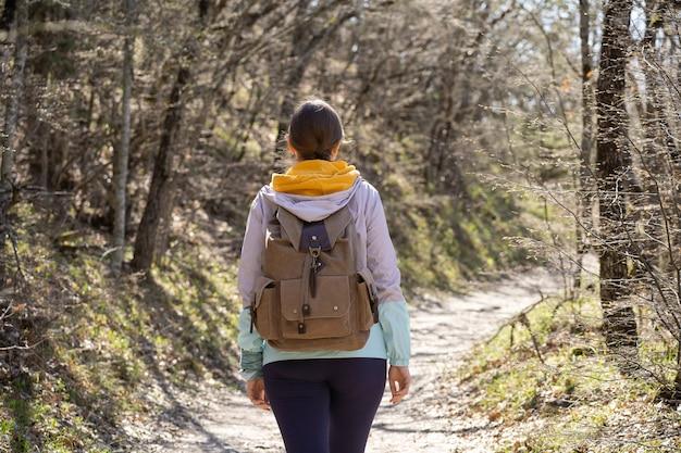 Una donna con un grande zaino cammina lungo un sentiero nel bosco. lungo viaggio a piedi. voglia di avventura e luoghi inesplorati.