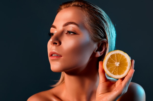 Donna con limone su una parete nera.