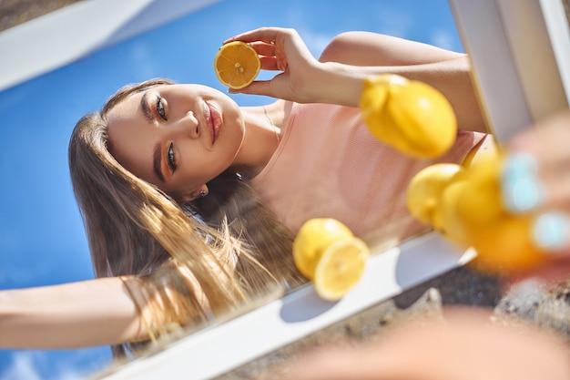Donna con un limone in mano, nutrizione della pelle di bellezza con vitamina c. cosmetici naturali per la cura della pelle del viso. giornata di sole cielo blu