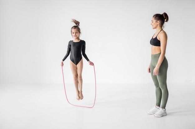 Donna con una bambina sull'allenamento di ginnastica ritmica