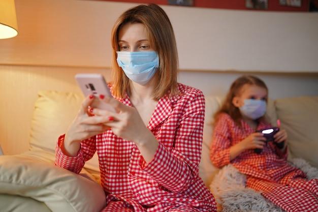 Donna con bambino a casa isolamento auto quarantena che indossa la maschera con smart phone per leggere le informazioni su covid-19