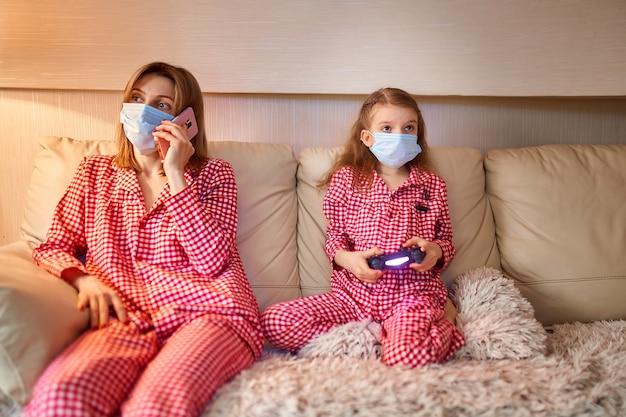 Donna con ragazzino a casa isolamento auto quarantena che indossa la maschera per il viso con smart phone parlando di covid-19