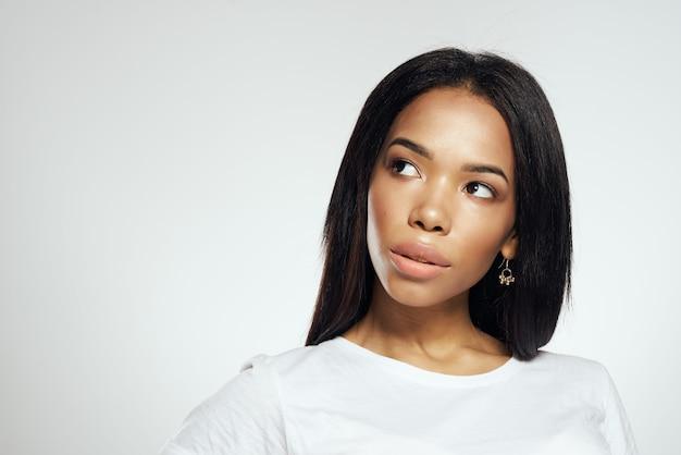 Donna con lunghi capelli neri in posa studio di cosmetici maglietta bianca