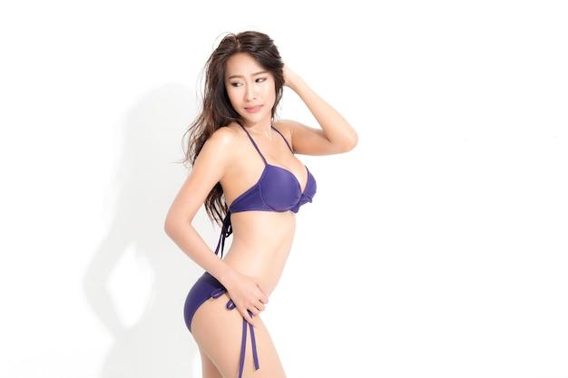 Donna con lunghi capelli castani che indossa un abito bikini viola in una moda estiva in posa isolato su bianco.