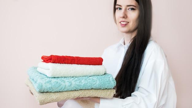 Donna con capelli lunghi che tiene una pila di asciugamani piegati