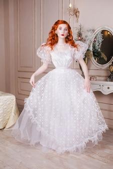 Donna con lunghi capelli rossi ricci in un abito da sposa vintage bianco con orecchini di perle bianche sulle orecchie. ragazza dai capelli rossi con la pelle pallida, gli occhi azzurri, un aspetto insolito e luminoso nella lussuosa camera da letto