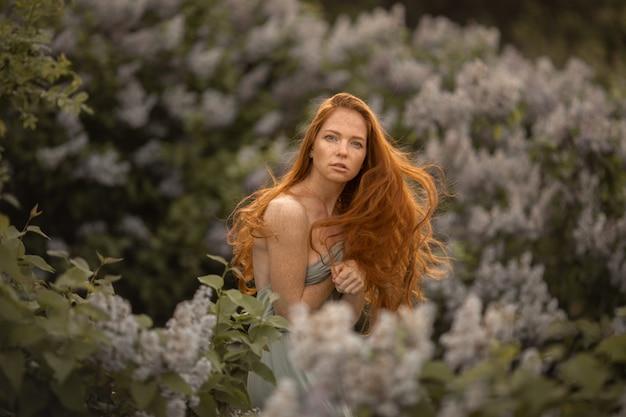 Donna con lunghi capelli rossi su uno sfondo di cespugli con fiori lilla