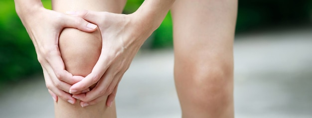 Una donna con molto dolore al ginocchio nel parco