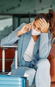 Donna con i bagagli in aeroporto parlando al telefono durante la pandemia