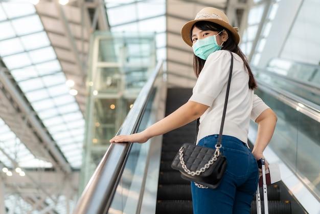 Donna con bagagli che indossa la maschera per il viso guardando fuori dal terminal in aeroporto