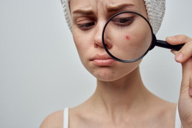Donna con una lente di ingrandimento in mano studio di cosmetologia