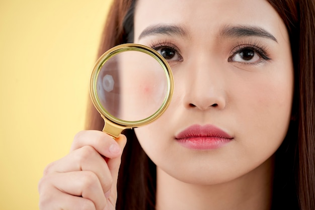 Donna con lente di ingrandimento isolata su sfondo giallo