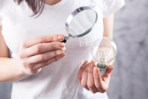 La donna con una lente d'ingrandimento esamina una lampadina. idea di studio del concetto