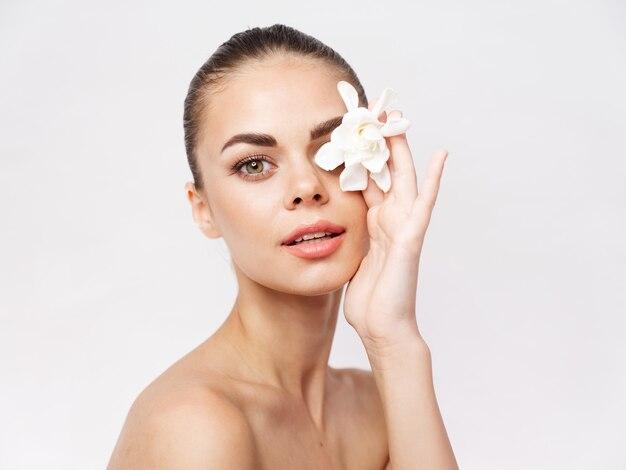 Donna con il trucco sul viso fiore bianco spalle nude vista ritagliata studio