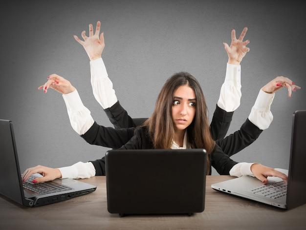 Donna con molte braccia che lavora con tre laptop