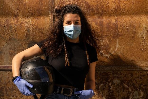 Donna con la maschera che tiene il casco della bici sopra metallico