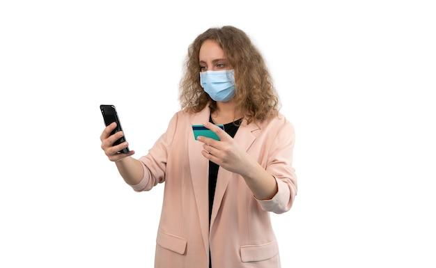 Donna con una maschera che effettua un acquisto online con il suo smartphone. tiene la carta di credito in una mano e il telefono nell'altra