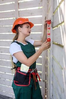 Donna con strumento di livello di misura sul sito in costruzione