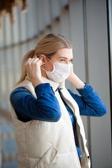 Donna con maschera facciale medica in aeroporto
