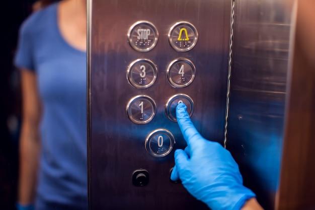 Donna con guanti medici spingendo il pulsante nell'ascensore. avvicinamento. concetto di igiene e assistenza sanitaria
