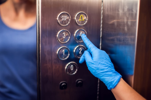 Donna con guanti medici spingendo il pulsante nell'ascensore. concetto di igiene e assistenza sanitaria