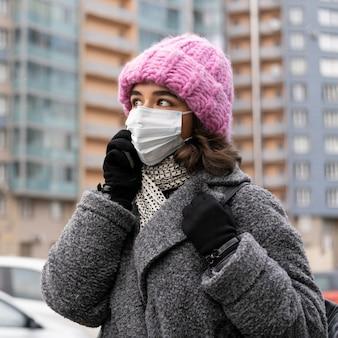 Donna con mascherina medica in città parlando al telefono