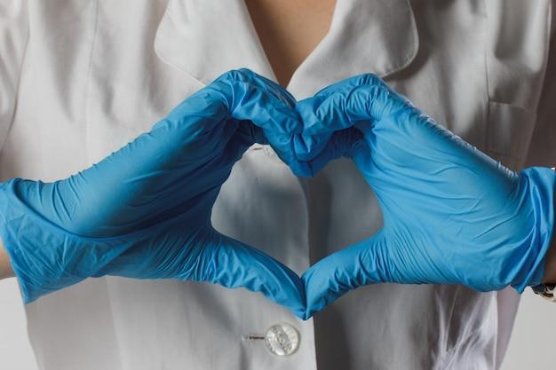 La donna con una maschera medica e le mani in un guanto di lattice mostra il simbolo del cuore. protezione corona