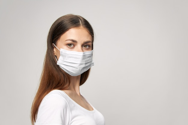 Donna con una mascherina medica sul viso in una maglietta bruna bianca su uno sfondo isolato copy space