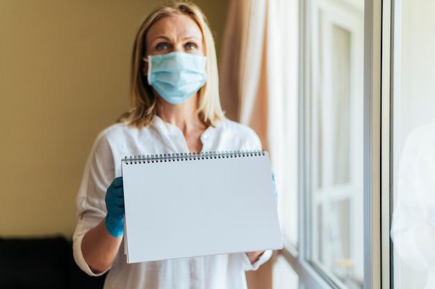 Donna con mascherina medica a casa tenendo il taccuino