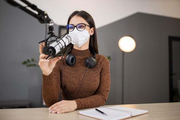 Donna con mascherina medica in uno studio radiofonico