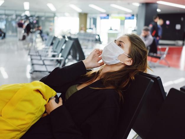 Donna con maschera medica seduta in attesa dei bagagli in aeroporto