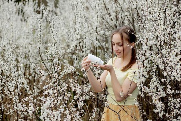 Donna con la medicina nelle mani lotta alle allergie primaverili all'aperto - ritratto di una donna allergica circondata da fiori di stagione