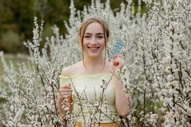 Donna con la medicina nelle mani lotta alle allergie primaverili all'aperto - ritratto di una donna allergica circondata da fiori di stagione.