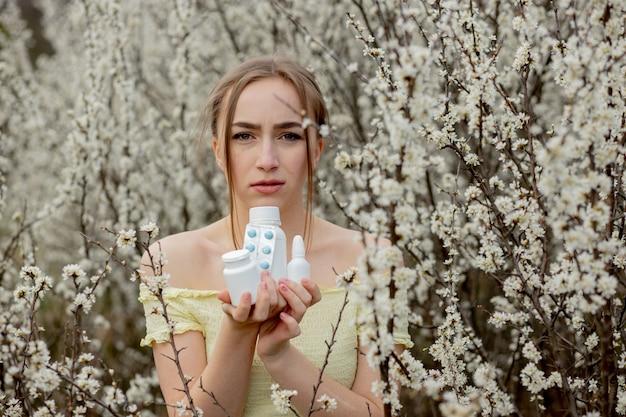 Donna con la medicina nelle mani combattere le allergie primaverili all'aperto - ritratto di una donna allergica circondata da fiori di stagione.