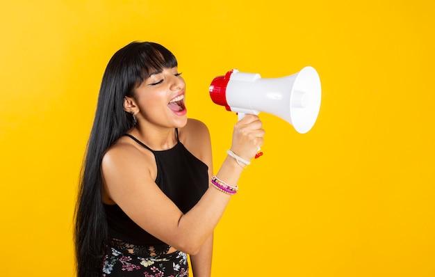 Donna con un megafono che urla, su sfondo giallo