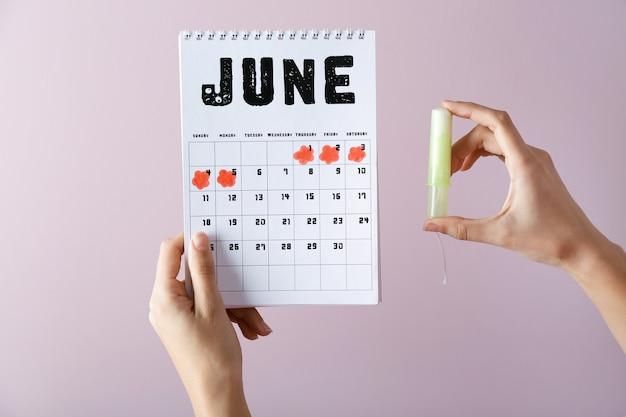 Donna con calendario mestruale e tampone su sfondo colorato