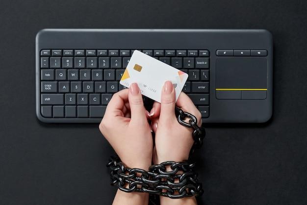 Donna con la carta di credito della tenuta della catena del metallo sopra la tastiera, concetto online di dipendenza di acquisto