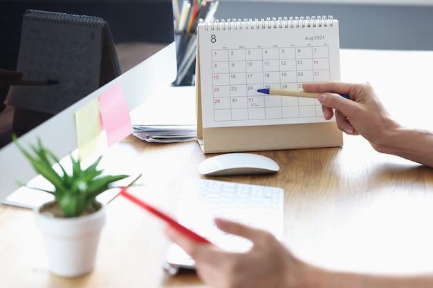 Donna con il telefono cellulare in mano che indica con la penna fino ad oggi sul primo piano del calendario da scrivania