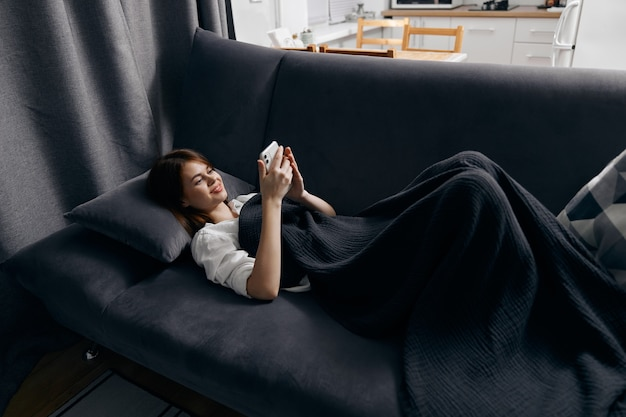 Una donna con un telefono cellulare giace su un divano grigio vicino alla finestra sullo sfondo