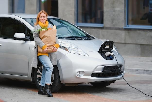 Donna con un telefono cellulare vicino alla ricarica di auto elettriche. ricarica del veicolo alla stazione di ricarica pubblica all'aperto. concetto di car sharing
